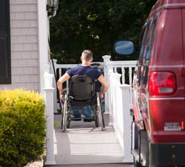 a photo of a man using a wheelchair to go up his ramp to his home